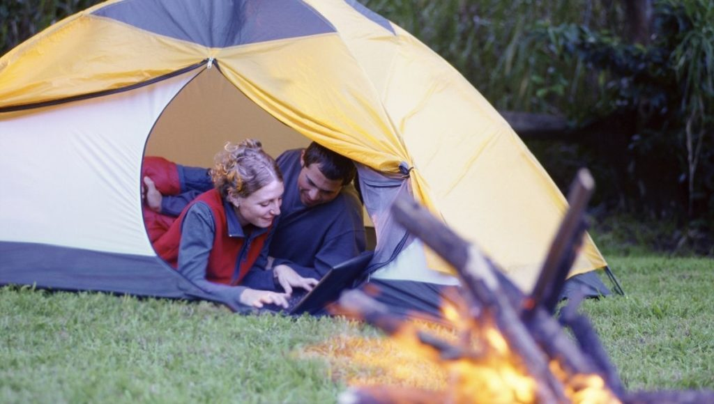 Two people using a laptop while camping. The Best Lightweight Laptop with Long Battery Life will be a great choice.