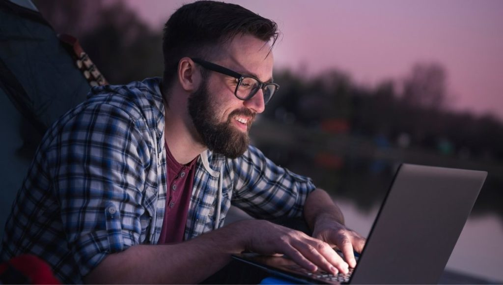 Man using a laptop in the dark while camping.