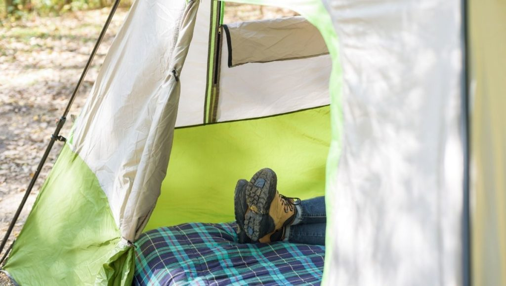 A man lying down on a bed in a tent wondering How to Make a Camping Cot More Comfortable