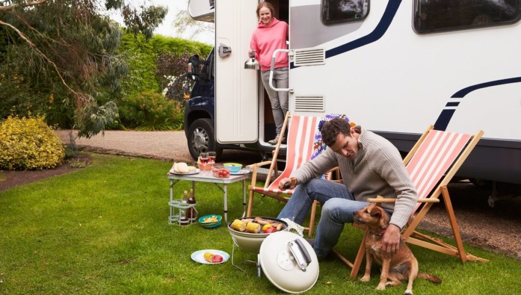 A couple enjoying the best RV BBQ with their dog