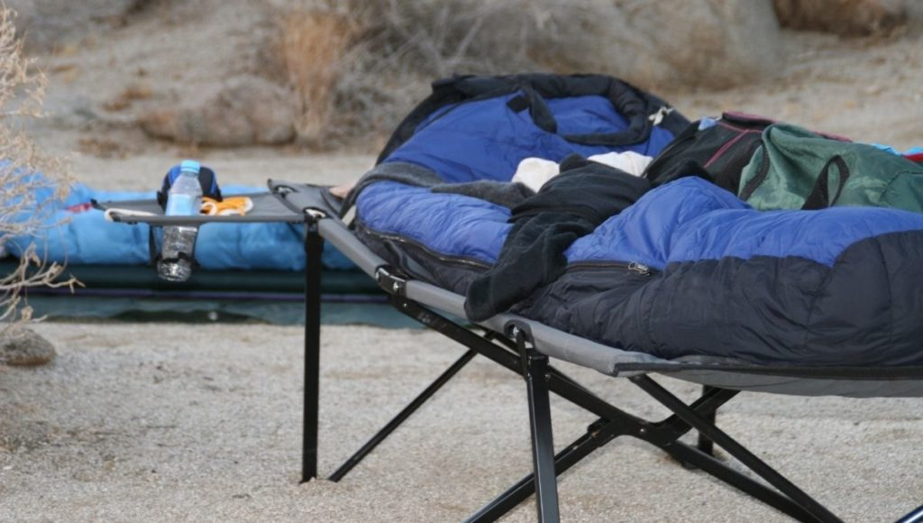 A camping bed on sand is not a great introduction to how to clean a camping cot
