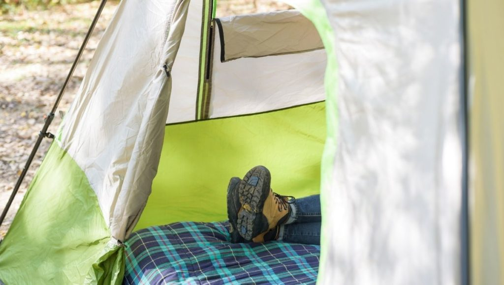 A man lying on a camping cot in a tent with muddy shoes on