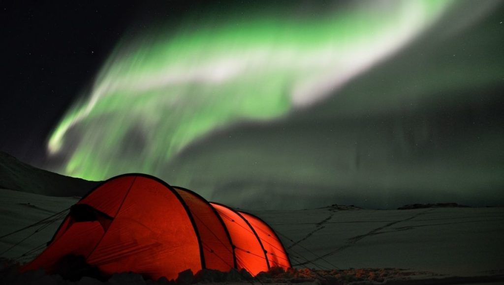A tent in the snow under the Northern Lights