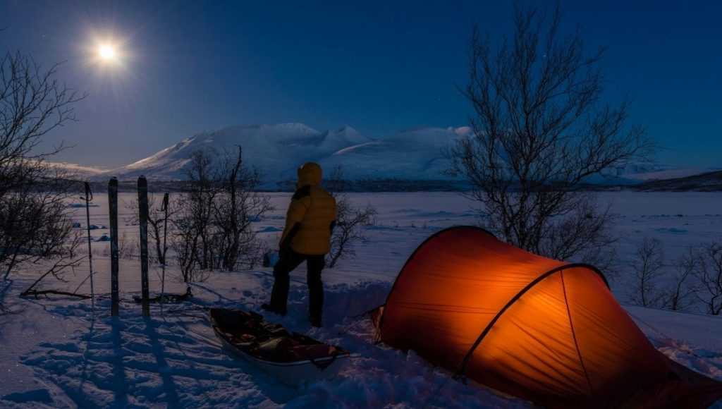 How To Stay Warm When Camping In Cold Weather in a tent on the snow