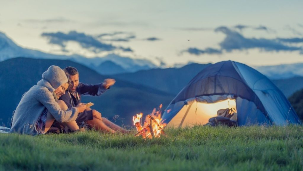 Best camping cot for two people. Two people camping, sat by a fire with a tent in the background