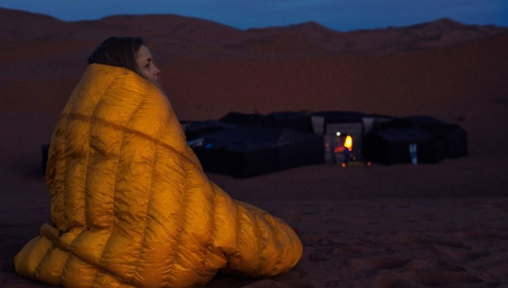 A girl wrapped up in a sleeping bag in the cold dessert at night