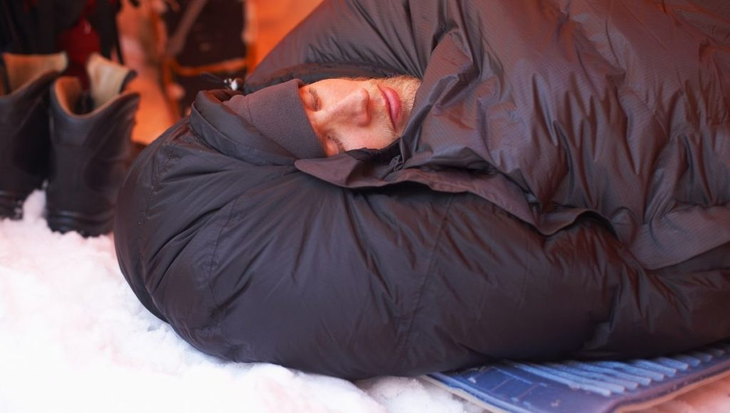 A man wrapped up warm in a sleeping bag with snow on the ground