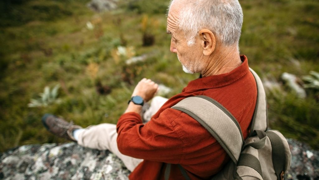 A hiking man checking smart watch