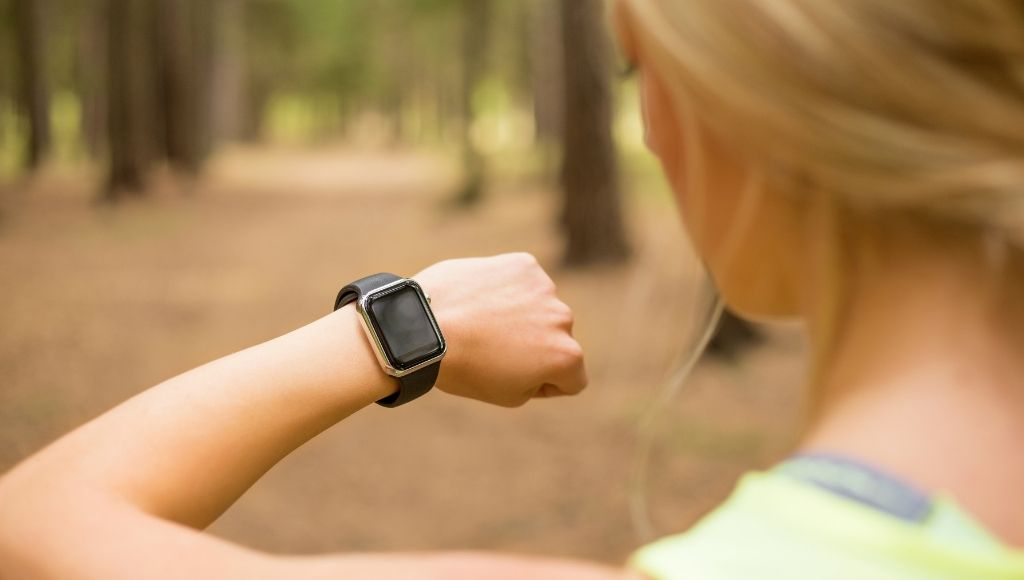 Female runner checks her gps watch