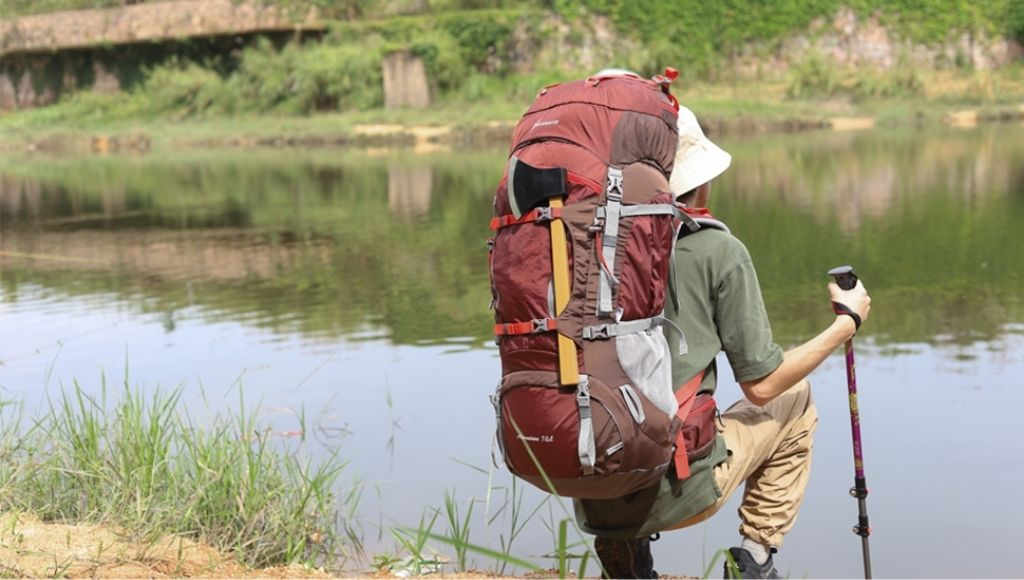 A man is looking at the river with a mountaintone 70l backpack on his shoulder.