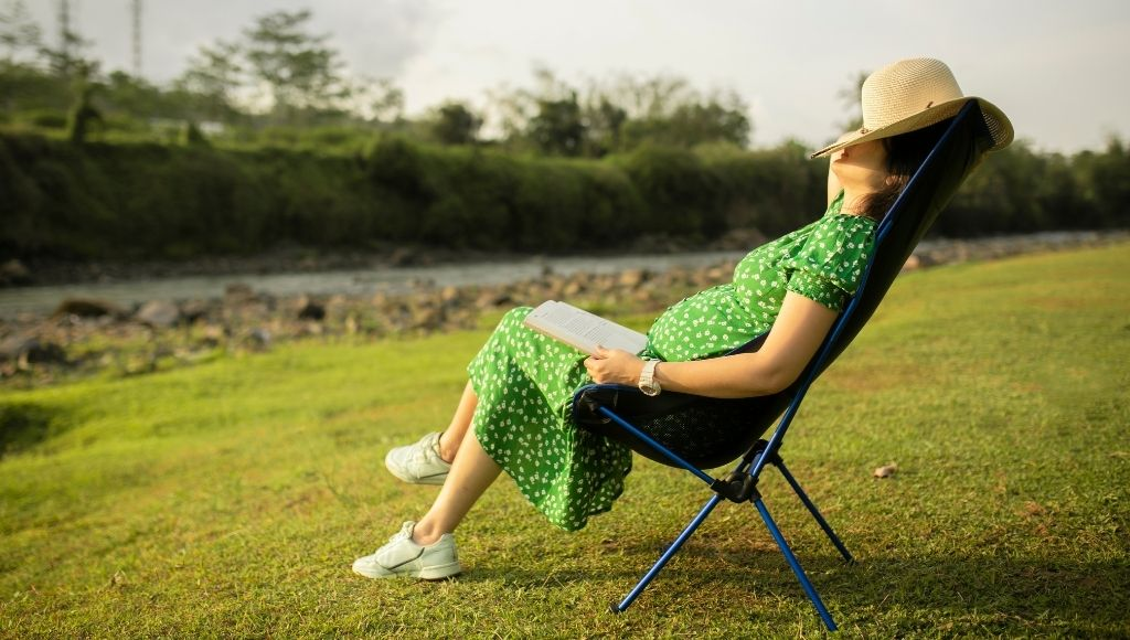 asian woman napping on camping helinox sunset chair in nature