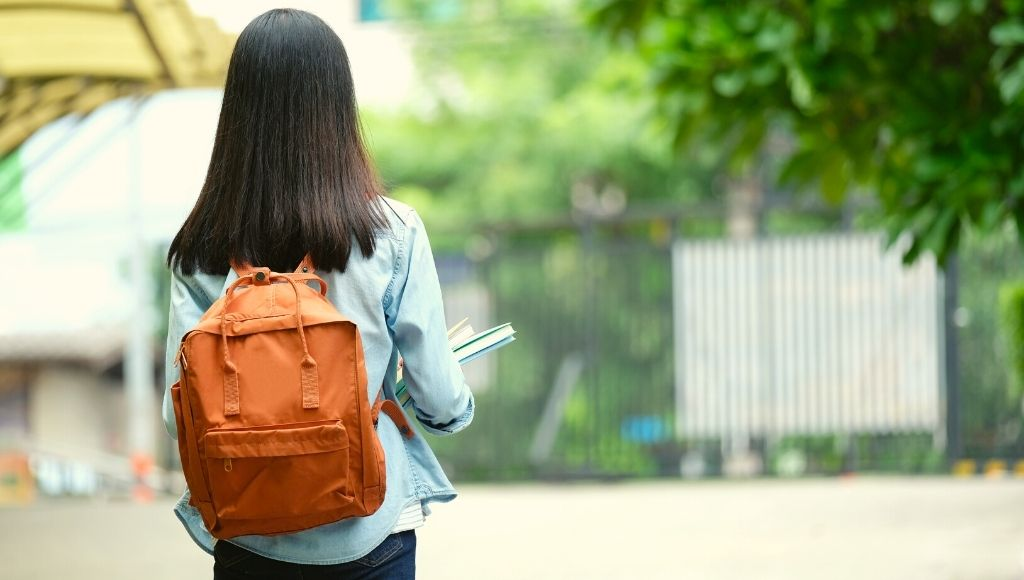Back of student girl holding books and carry school Daypack while walking in school campus background, education, back to school concept