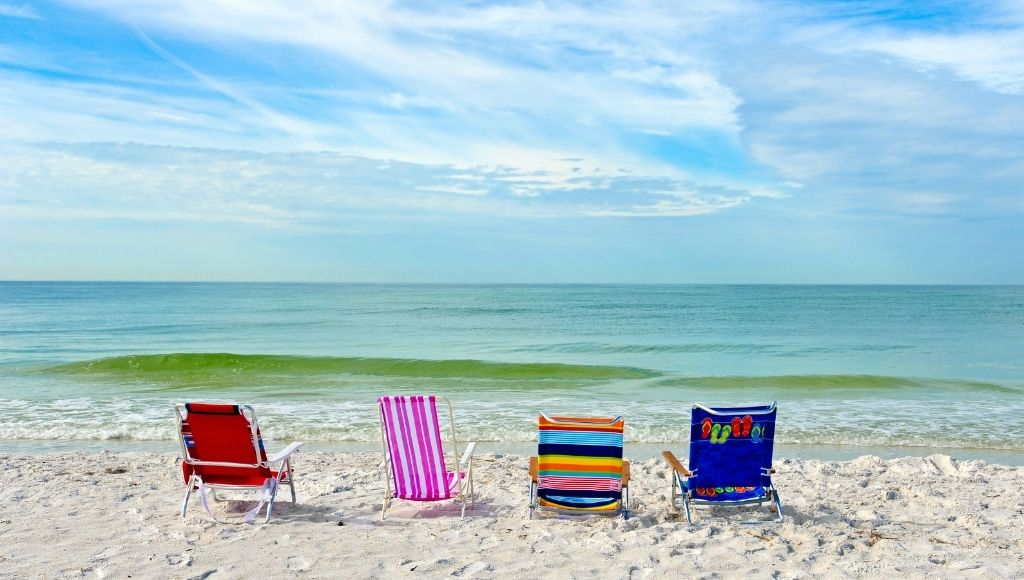 Four colorful campaign chairs and beach chairs on the beach