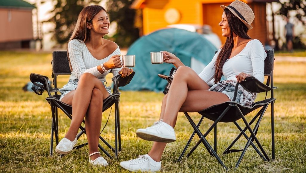 Two women sit in Camping Lawn Lounge Chair enjoy their Camping