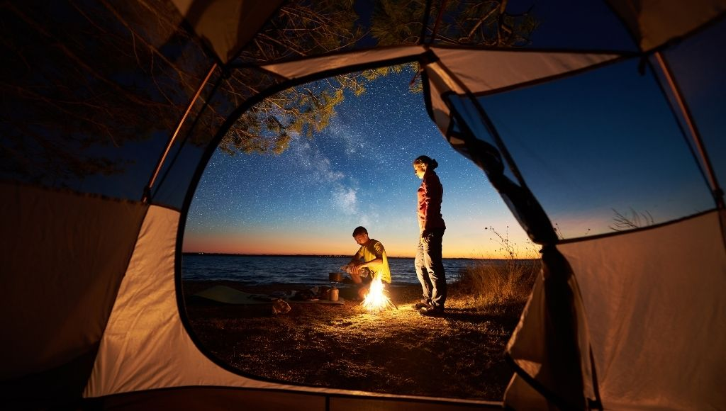 A couple is lighting a campfire outside the tent