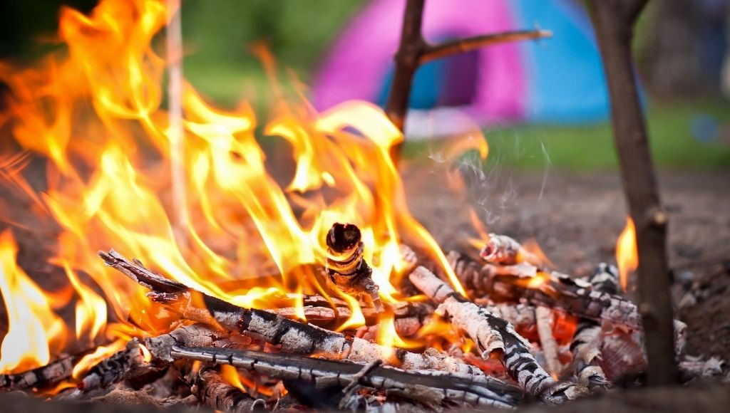 A burning campfire outside the camp