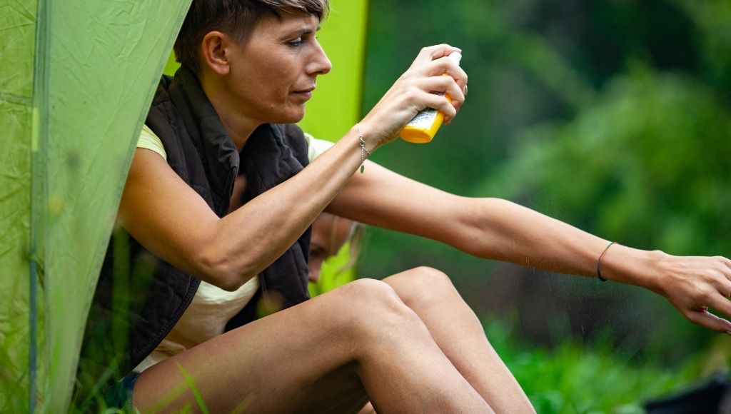 A woman is spraying her body to get rid of mosquitoes