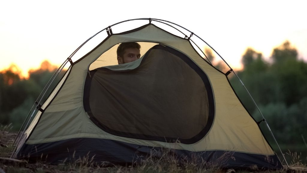 A boy into a zip closed camping tent
